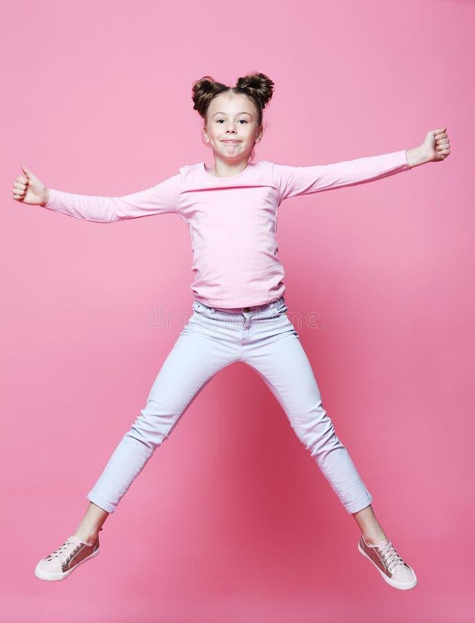 a menina engraçada da criança vestiu o salto ocasional no fundo cor-de-rosa foto de stock