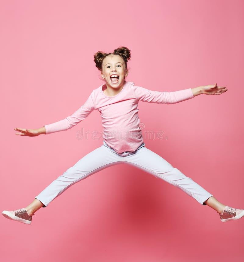 a menina engraçada da criança vestiu o salto ocasional no fundo cor-de-rosa imagem de stock