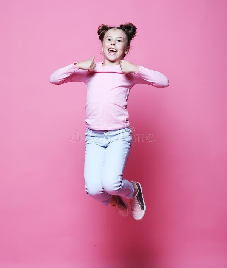 a menina engraçada da criança vestiu o salto ocasional no fundo cor-de-rosa fotografia de stock royalty free