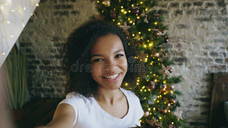 Menina engraçada da raça misturada que toma imagens do selfie na câmera do smartphone em casa perto da árvore de Natal fotos de stock royalty free