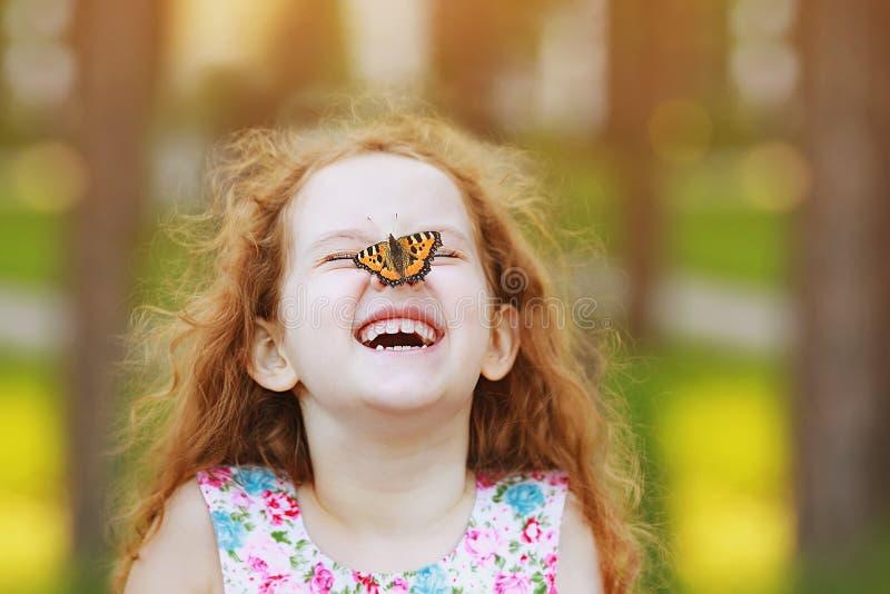Menina engraçada de riso com uma borboleta em seu nariz imagem de stock