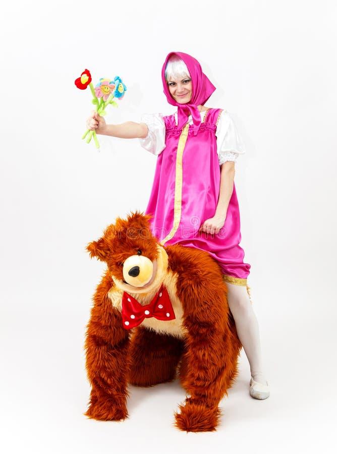 Menina engraçada do conto de fadas que senta para cima um homem no traje do urso imagens de stock
