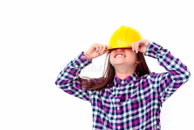 Menina engraçada do coordenador com um capacete amarelo isolado no backg branco fotografia de stock royalty free