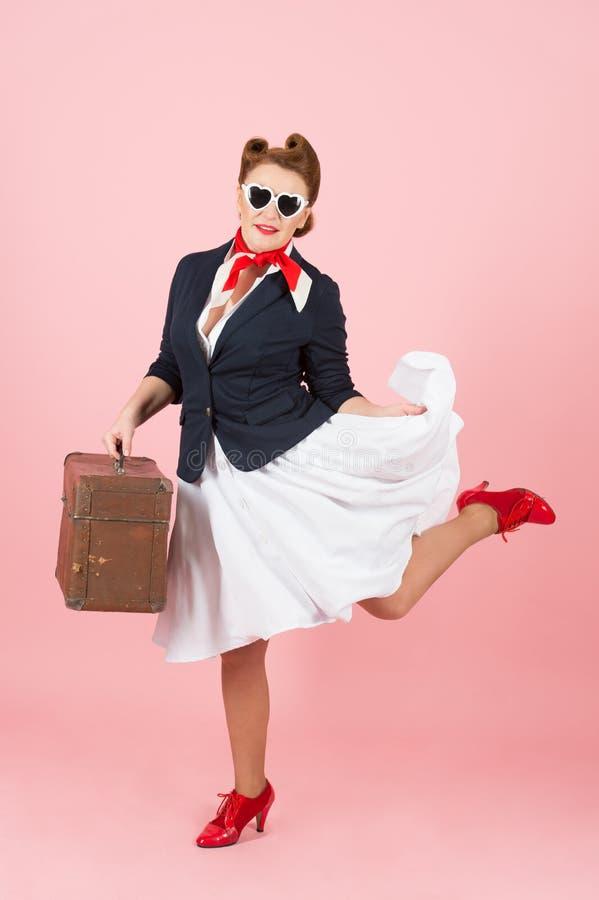 Menina engraçada do viajante com mala de viagem e os óculos de sol pretos Mulher moreno no estilo do pino-acima com caso do vinta imagem de stock
