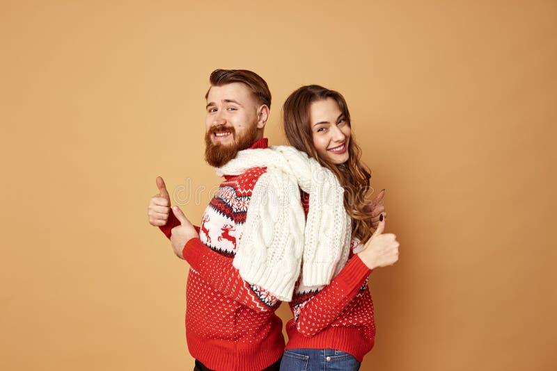 A menina engraçada e um indivíduo vestido em camisetas vermelhas e brancas com cervos e o lenço feito malha branco estão para trá fotos de stock