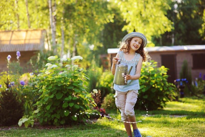 menina engraçada feliz da criança no chapéu do jardineiro que joga com lata molhando fotografia de stock