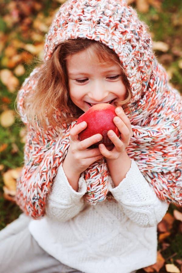 Menina engraçada feliz da criança no lenço feito malha acolhedor que come a maçã fresca no jardim do outono fotos de stock