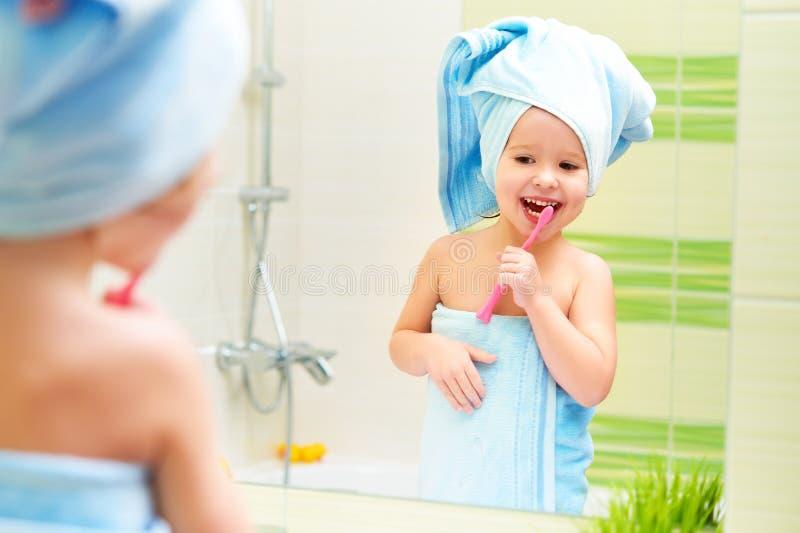 A menina engraçada limpa os dentes com a escova de dentes no banheiro fotos de stock royalty free