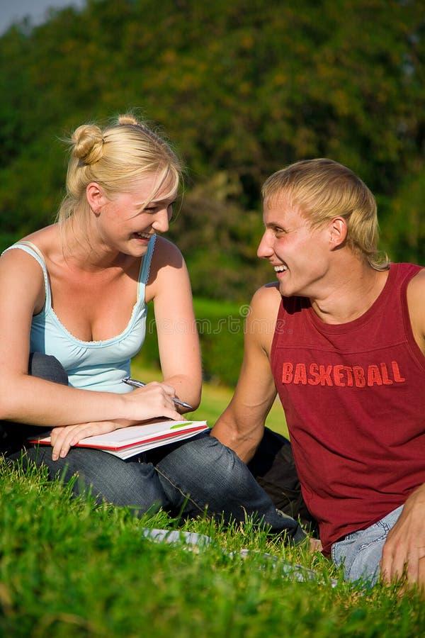 Menina engraçada loura com o menino bonito no parque imagens de stock
