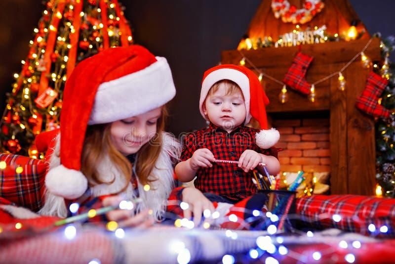A menina engraçada no chapéu de Santa escreve a letra a Santa e a seu irmão do liitle imagem de stock