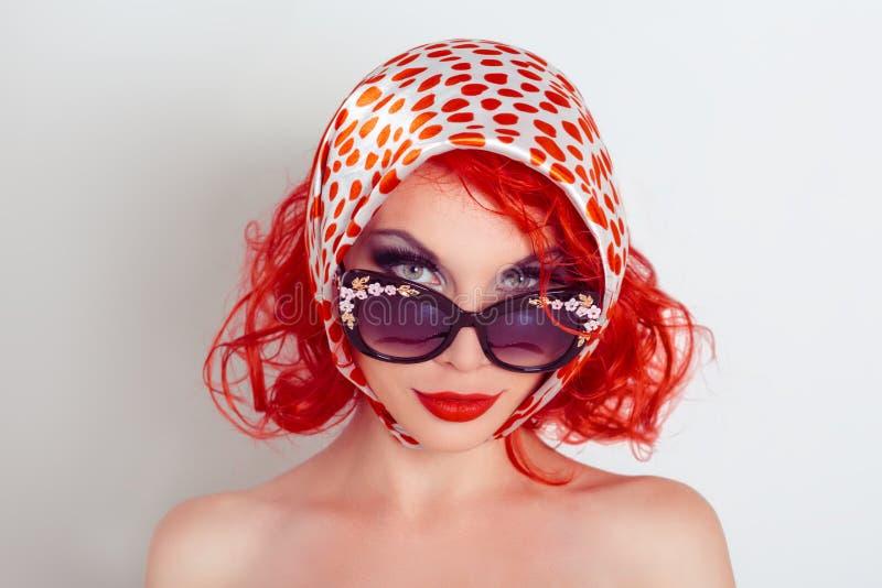 Menina engraçada no estilo retro Foto do estúdio da menina nos óculos de sol e em um divertimento do lenço imagem de stock royalty free