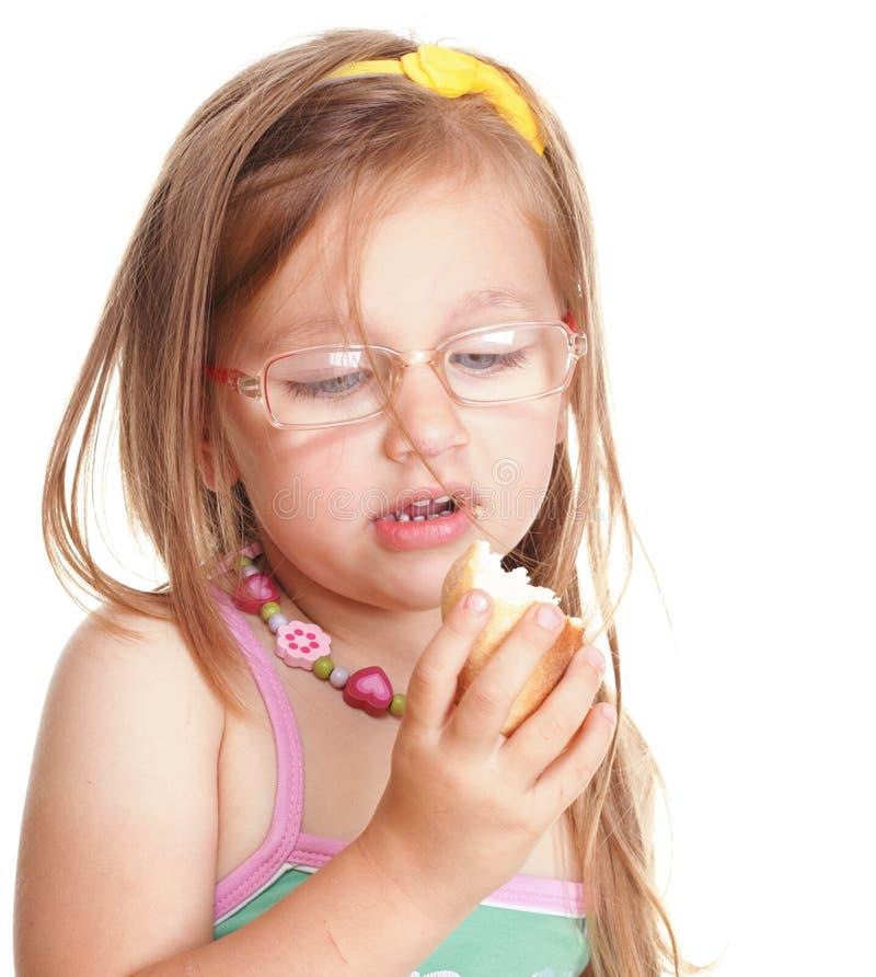 Menina engraçada nos vidros que come o pão que faz o divertimento isolada imagens de stock royalty free