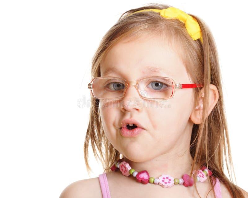 Menina engraçada nos vidros que come o pão que faz o divertimento isolada fotografia de stock