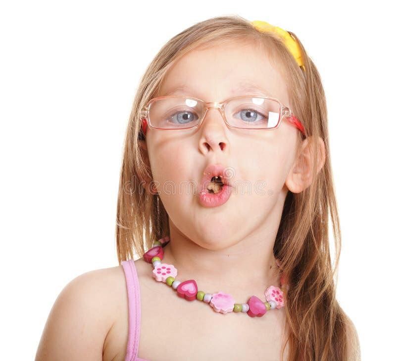 Menina engraçada nos vidros que come o pão que faz o divertimento isolada fotografia de stock royalty free