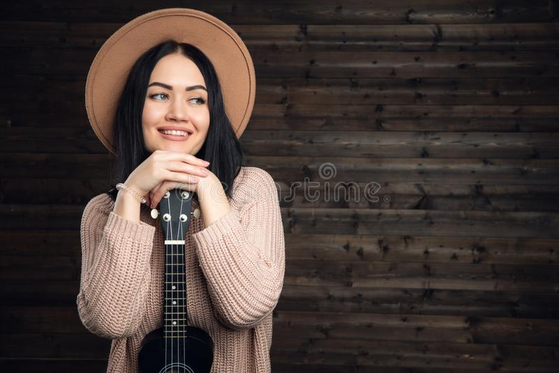 Menina engraçada nova do moderno que tem o divertimento e que joga na guitarra pequena, no canto e na dança da uquelele chapéu ve imagem de stock