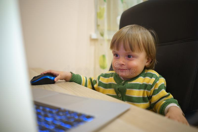Menina engraçada pequena bonito que usa o portátil imagem de stock royalty free