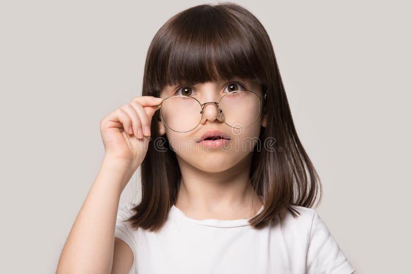 Menina engraçada que abaixa os vidros que olham a perplexidade da sensação da câmera foto de stock