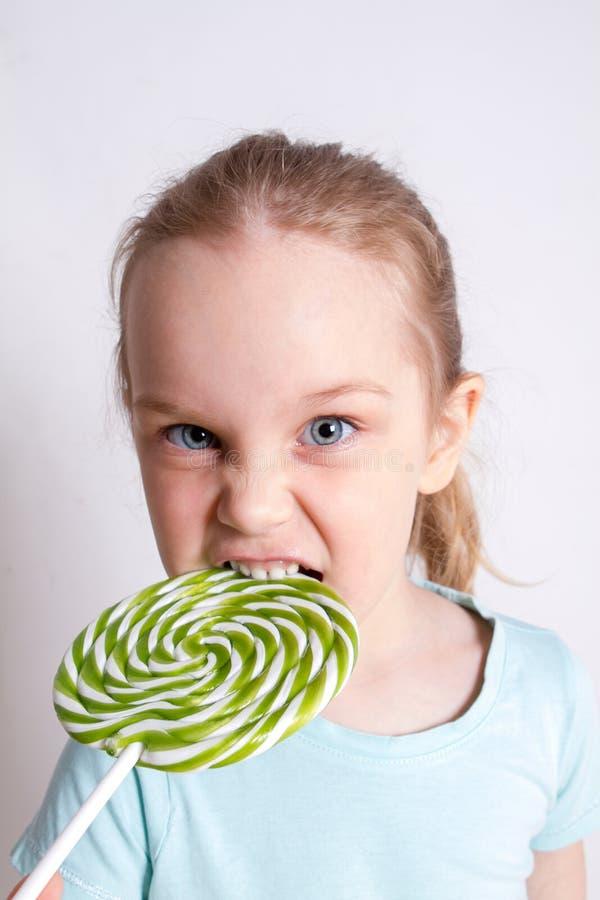 Menina engraçada que come o pirulito foto de stock royalty free
