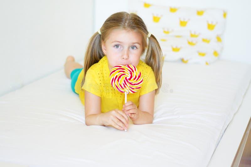 Menina engraçada que come o pirulito grande do açúcar foto de stock