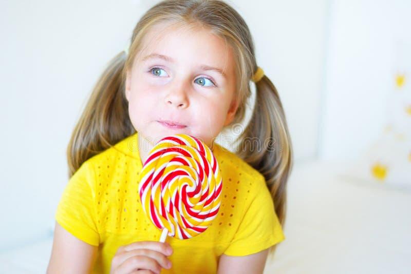 Menina engraçada que come o pirulito grande do açúcar imagem de stock
