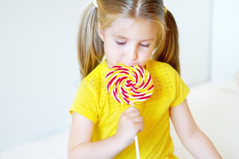 Menina engraçada que come o pirulito grande do açúcar fotos de stock royalty free