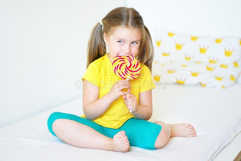 Menina engraçada que come o pirulito grande do açúcar imagens de stock