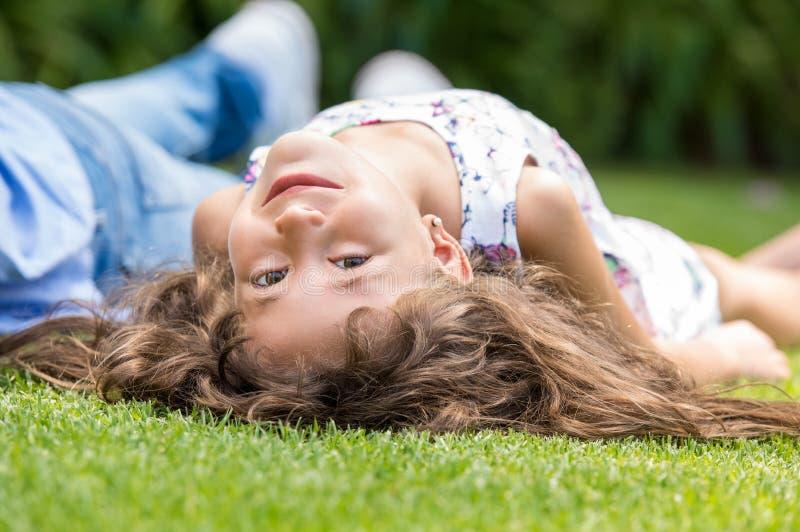Menina engraçada que encontra-se na grama fotografia de stock royalty free