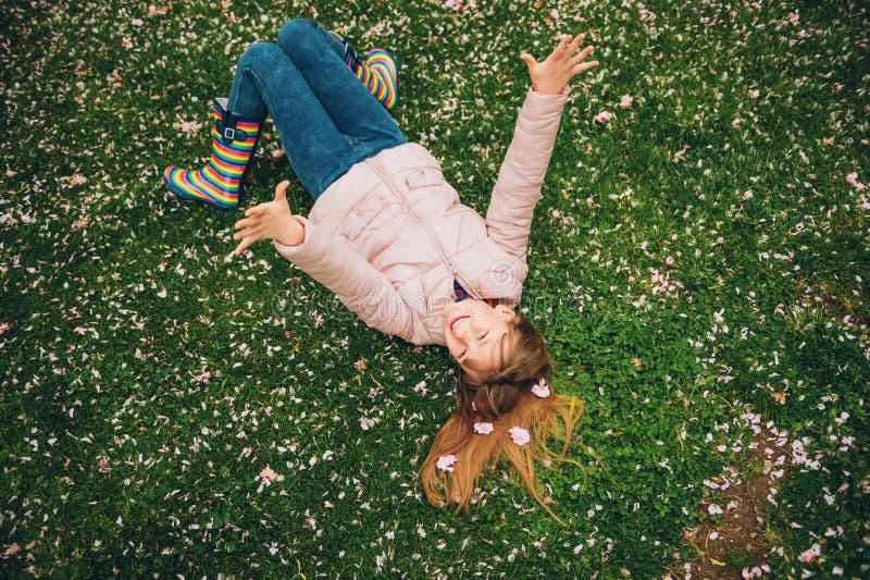 Menina engraçada que encontra-se na grama verde-clara, jogando com as pétalas macias da flor no parque da mola imagem de stock royalty free