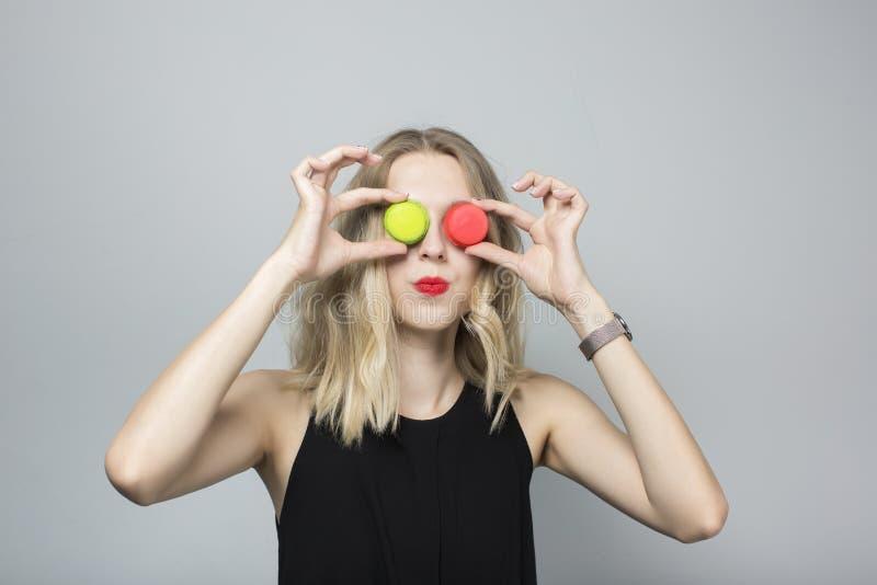 Menina engraçada que faz as caras com os dois bolinhos de amêndoa colocados em vez dos olhos A menina tem o cabelo louro encaraco fotos de stock