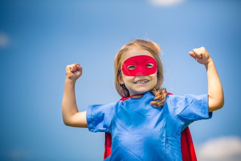 Menina engraçada que joga o super-herói do poder fotografia de stock royalty free