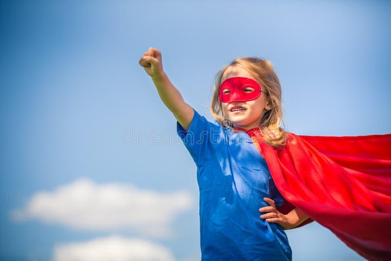 Menina engraçada que joga o super-herói do poder foto de stock