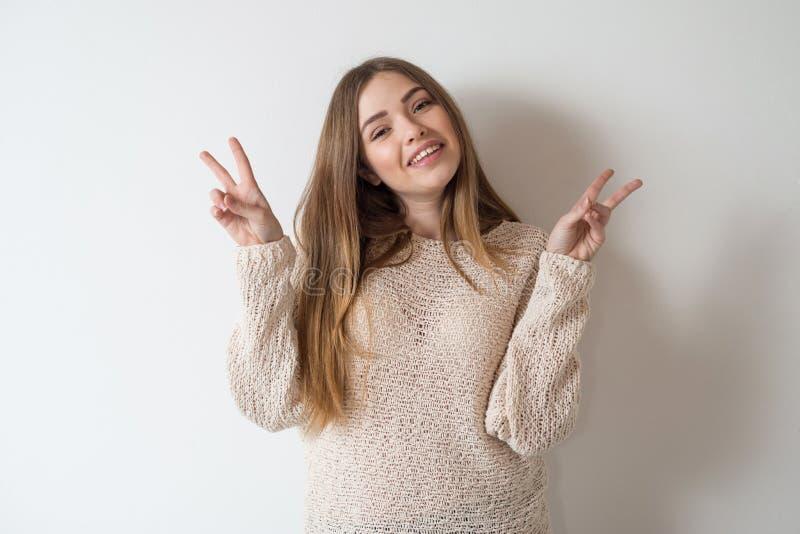 Menina engraçada que mostra o sinal de paz fotografia de stock