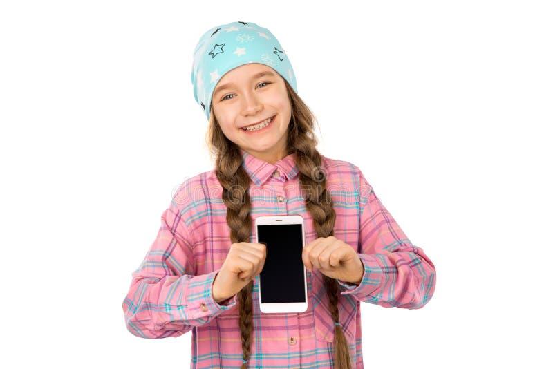 Menina engraçada que mostra o telefone esperto com a tela vazia no fundo branco Jogando jogos e vídeo do relógio fotos de stock
