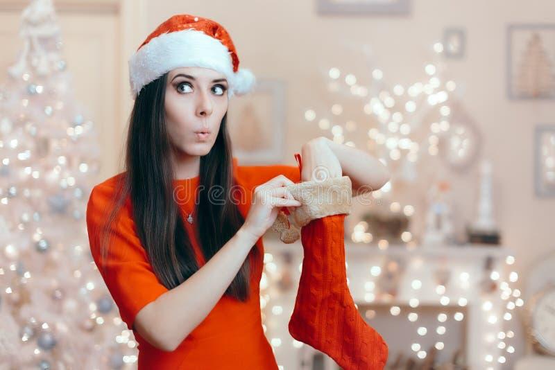 Menina engraçada que procura seu presente em uma meia do Natal imagens de stock royalty free