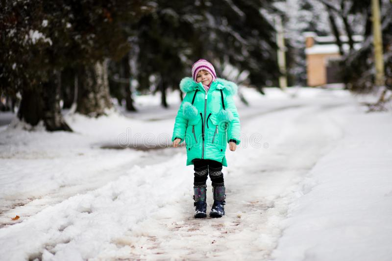 Menina engraçada que tem o divertimento no parque bonito do inverno imagens de stock