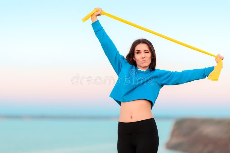 Menina engraçada que tenta dar certo com faixa da ioga fotografia de stock