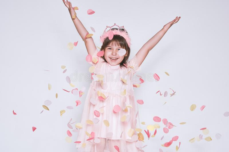 A menina engraçada que veste o vestido cor-de-rosa no tule com a coroa da princesa na cabeça nas mãos brancas da elevação do fund imagem de stock