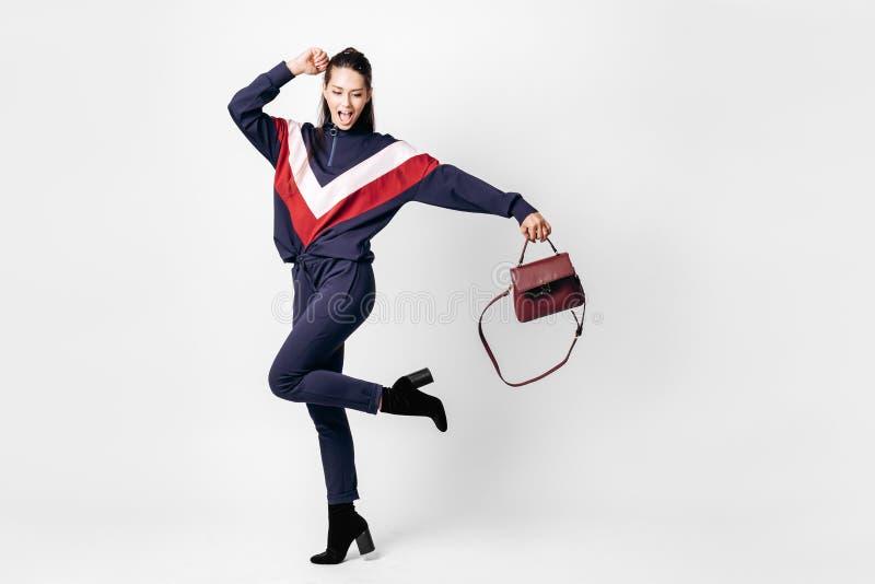 A menina engraçada vestiu-se no terno azul desportivo com uma cópia vermelha e branca em uma camiseta e coloca saltos poses com o fotografia de stock