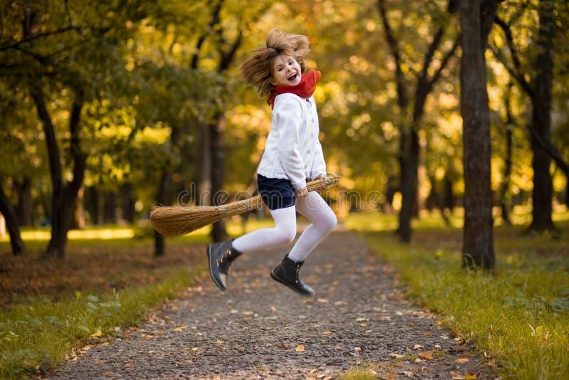 A menina engraçada voa na vassoura no outono fotos de stock