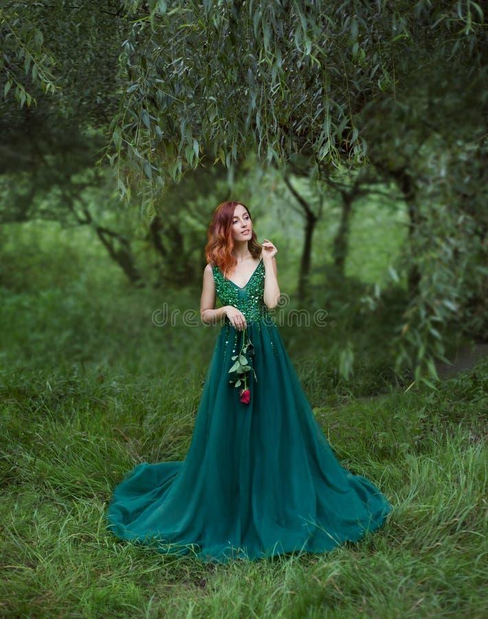 A menina enigmática no esclarecimento da grama está guardando uma rosa nas mãos imagens de stock royalty free