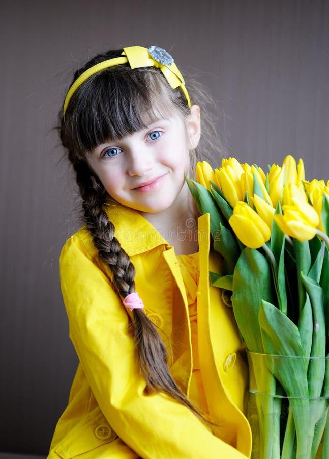 Menina ensolarada da criança com o ramalhete de tulips amarelos fotografia de stock royalty free