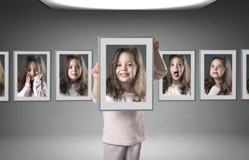 Menina entre lotes de seus retratos fotografia de stock