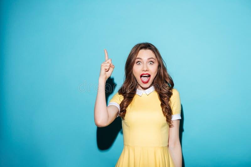 Menina entusiasmado bonita no vestido que aponta o dedo acima no copyspace imagem de stock royalty free