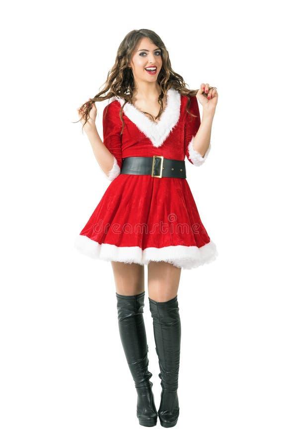 Menina entusiasmado brincalhão de Santa que guarda o cabelo que sorri e que olha a câmera foto de stock
