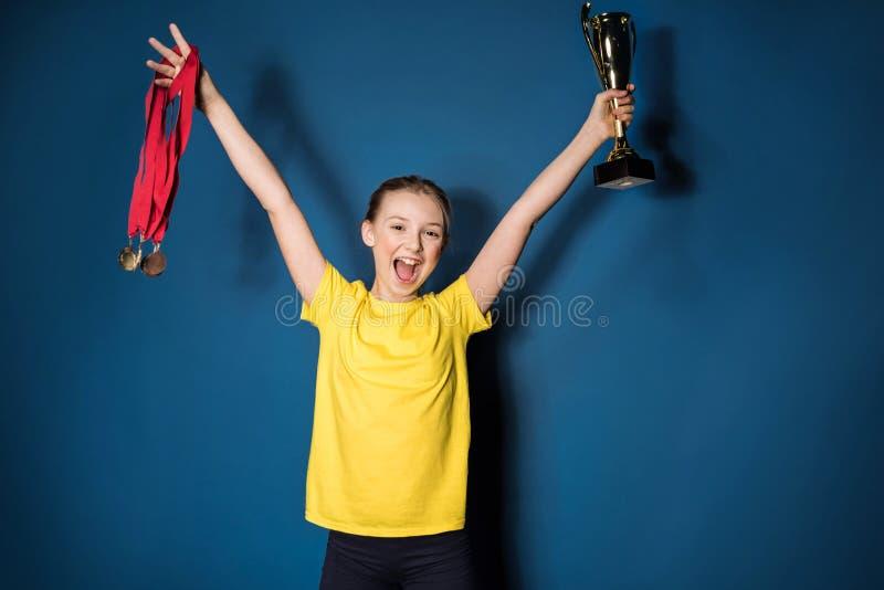 Menina entusiasmado com medalhas e copo do troféu foto de stock royalty free