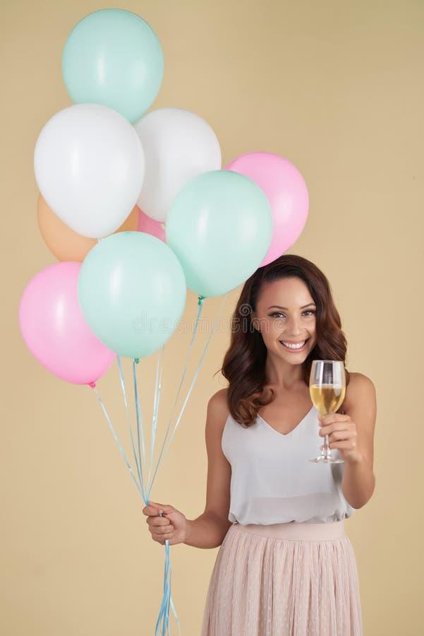 Menina entusiasmado com os balões que aumentam o copo de vinho foto de stock royalty free