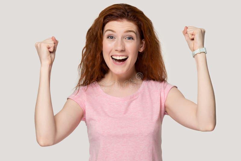 A menina entusiasmado do ruivo sente eufórico sobre o sucesso fotografia de stock royalty free