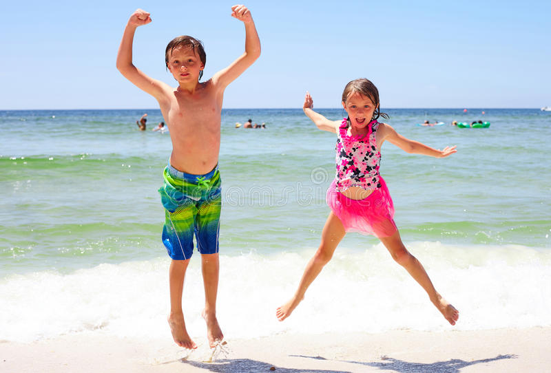 Menina entusiasmado e menino que saltam junto na praia imagem de stock royalty free