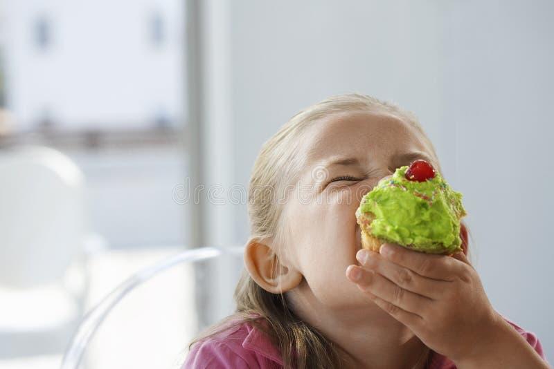 Menina entusiasmado que come o queque foto de stock