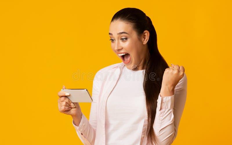 Menina entusiasmado que gesticula sim e que olha Smartphone Tiro do est?dio imagem de stock royalty free